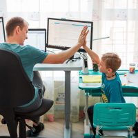 Father with kid working from home during quarantine. Stay at home, work from home